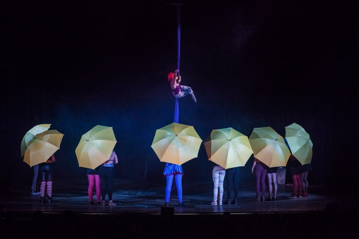 No palco, atores com guarda-chuvas amarelos assistem a chegada da protagonista do espetáculo de teatro Decadenta