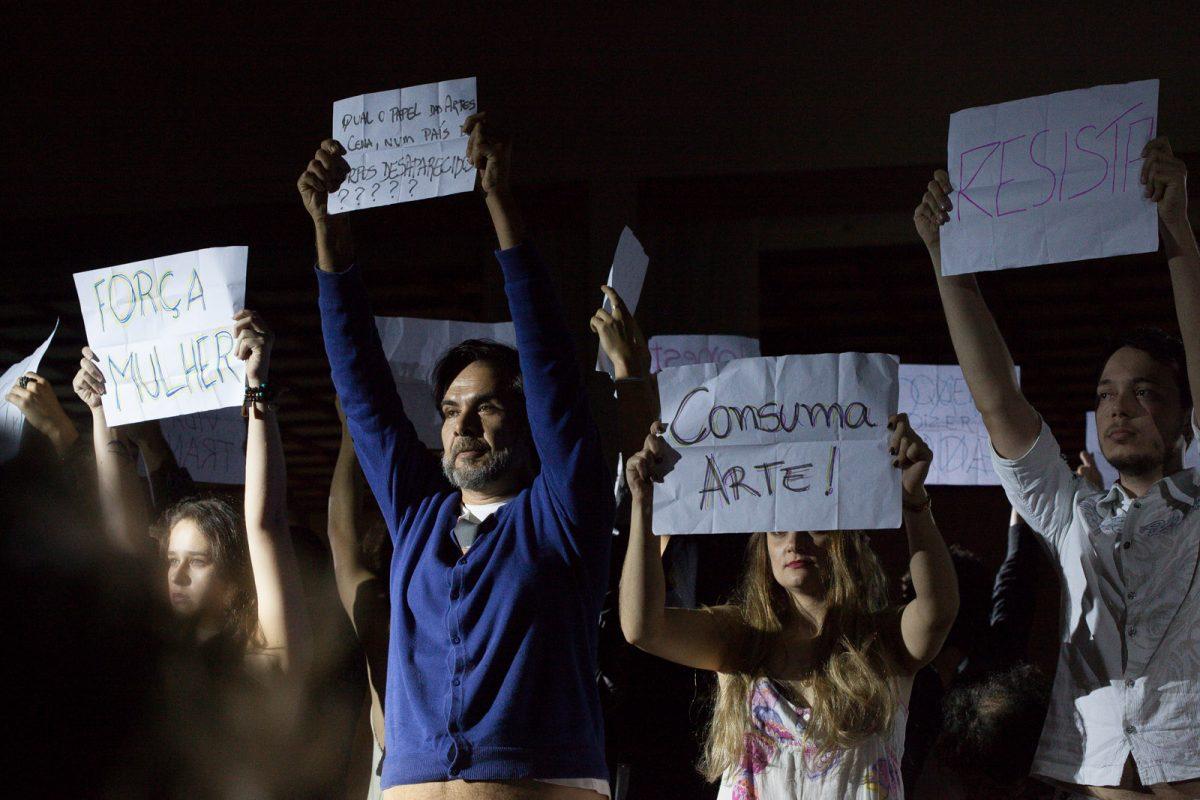 """Artistas mostram cartazes com frases de protesto (""""Força, Mulher"""", """"Consuma Arte!"""", """"Resista"""") em encerramento de Festival de Teatro em Bumenau"""