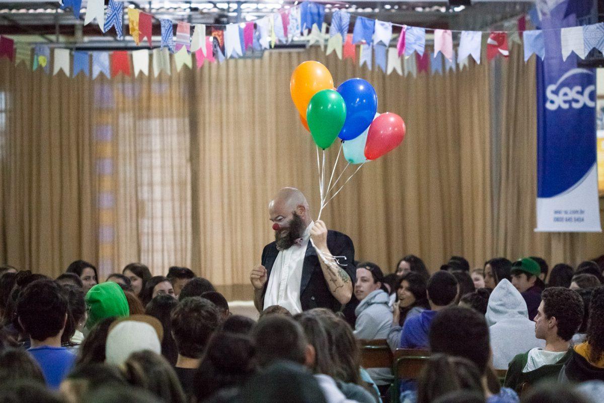O ator James Beck em meio ao público durante o espetáculo clown É Tentando Que Se Desiste (Cia Carona de Teatro - Blumenau), na EEB Professor Honório Miranda (Gaspar)
