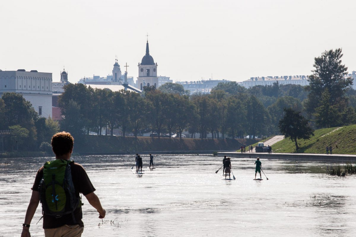 Tourists and locals enjoy summertime by Neris River, in Vilnius Lithuania