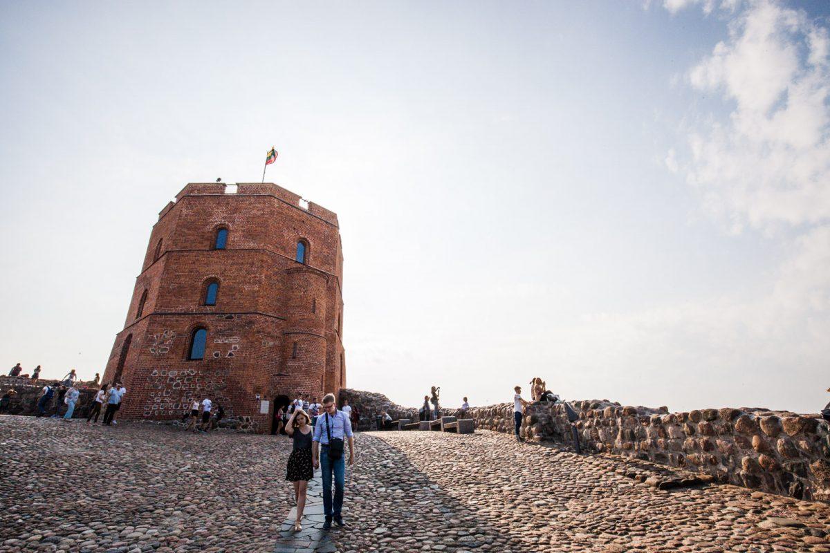 Casal caminha com outros turistas na Torre de Gediminas, local turístico em Vilnius, na Lituânia